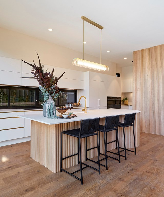**Week 6, Kitchen** Luke and Jasmin incorporated a curved timber feature wall and matching island bench into their kitchen which created a strong connection with the other rooms in their home, namely their bathrooms.