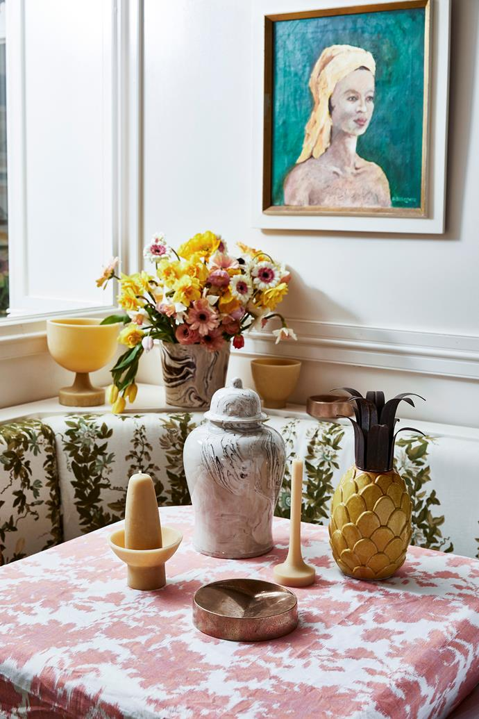 **On table, from left:** 'Floral Trail' fabric in Coral, $75/m, No Chintz. Brown marbled ginger jar, $350, Pigott's Store. Tony Assness 'Pillar on stand' candle in Large, $80, and 'Taper' candle in Medium, $60/35cm, both House Of Heras. 'Vide Poche Rond XL' dish in Bronze, $380, Henry Wilson. Vintage pineapple, $125, The Bay Tree. On shelf, from left: Tony Assness 'Chalice' candle, $217/tall, and 'Small Bowl with insert' candle, $72, both Bess. Brown marbled planter, $160, Pigott's Store. 'Vide Poche Rond' dish, $245, Henry Wilson