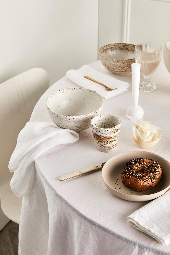 **On table, from left:** 100% linen tablecloth in White, $150/medium, and napkins in White $40/set of 4, all In Bed. Granola bowls, $55, and Long back cups, $45, all Porch Ceramics. Gold fork, $59/ part of a 5-piece cutlery set, West Elm. Sabre 'Bistrot' dinner knife in Ivory, $20.25, The Bay Tree. 'Pebble' cereal bowl in Dust, $47, Mud Australia. 'Margot' candle in White, $19, Maison Balzac. 'Beetle' resin dish in Cream Swirl, $50, Dinosaur Designs. 'Fire' tumbler, $49.95/set of 2, Riedel. Simone Karras 'Raku' vessel in White, $180/small, Jardan.