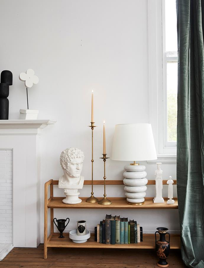 Flower sculpture (on fireplace), $450, Den Holm. SCP 'Agnes' long bookshelves in Oak, $3165, Hub Furniture. **On top shelf, from left:** Bust, stylist's own. Vintage brass candle holders, $645/part of a set of 3, Becker Minty. Kelly Wearstler 'Phoebe' stacked table lamp in Antique White with linen shade, $1795, Becker Minty. 'Caryatid Female Figure' sculpture, $290, and 'Iniohos Statue' sculpture, $89, both Mercer & Lewis.'Delhi' velvet curtain in Celadon, $289, Montmartre.