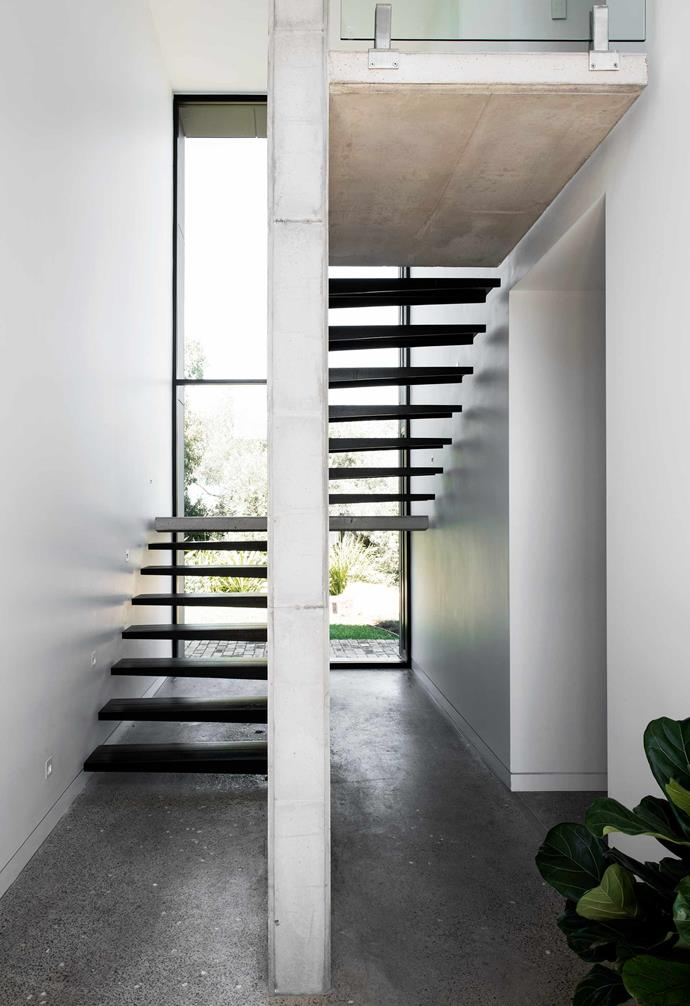**Staircase** One of the home's most striking features is the foyer, with a vertical concrete wall and 'suspended' steel steps to the main bedroom.