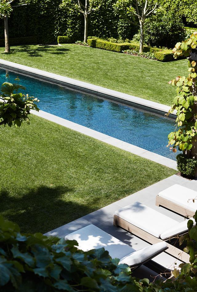 """A sleek lap pool runs through the middle of this lovely [Paul Bangay-designed garden](https://www.homestolove.com.au/melbourne-home-with-french-and-belgian-influence-6435