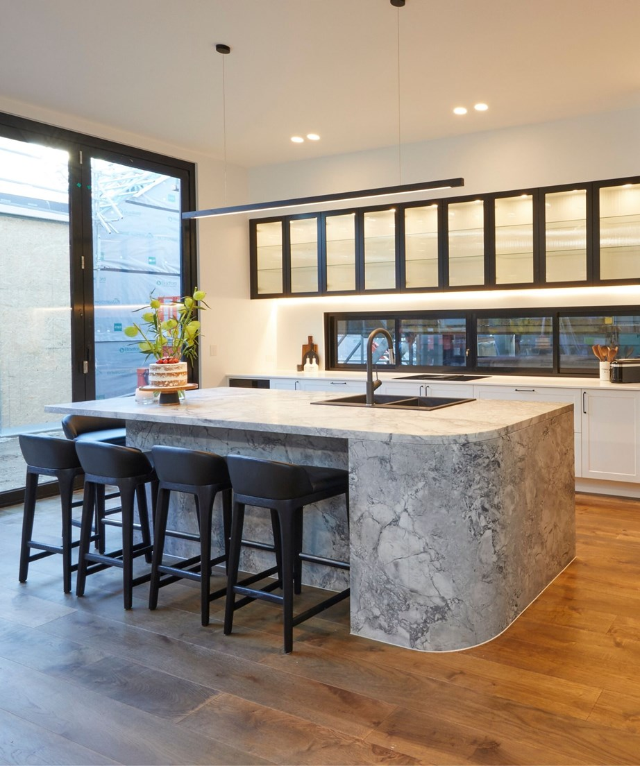 """**Week 6, Kitchen** Sarah and George's curved island bench made out of natural stone turned heads during kitchen week and even lured Darren Palmer in for a cuddle come judging. """"Just look at this detail,"""" said Darren, admiring the craftsmanship that went into creating this monolith. The broadline glass in the overhead cabinetry nods to the 1940s heritage of the home, adding a retro touch to an otherwise modern, monochrome kitchen."""