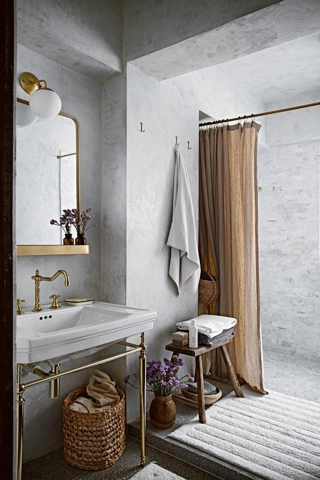 """Textural plaster-finished surfaces and sophisticated brass accents are the standout features of the bathroom in this [culinary blogger's apartment in Hong Kong](https://www.homestolove.com.au/blogger-apartment-hong-kong-21526