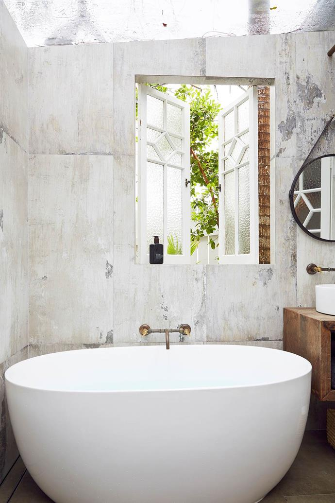 """The beauty of existing features and an aged patina is hero of this bathroom. Concrete-look tiles with a gorgeous aged grain, brass taps and a timber vanity are complemented by a modern basin and deep egg bath which keeps the look more luxe than 'old-fashioned', to suit it's [Byron Bay beach house home](https://www.homestolove.com.au/beach-house-decorating-ideas-20822