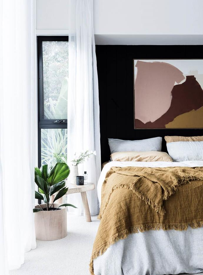 "An abstract artwork brings a splash of colour to the bedroom's black feature wall in this [Byron Bay home](https://www.homestolove.com.au/modern-coastal-interior-ideas-20679|target=""_blank""), while sheer curtains pay homage to the room's ample natural light. Photo: Maree Homer 