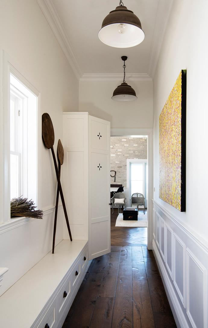 In the hallway, antique bread paddles from Dusty Luxe ornament the Steves Joinery cupboards. The painting is by Bibi Barba.