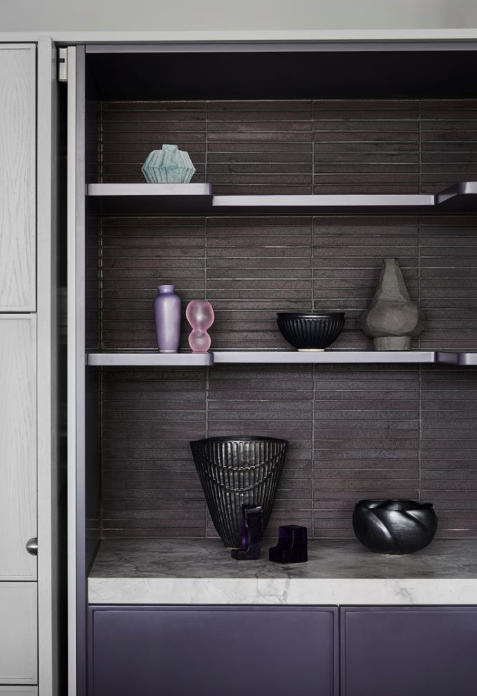 The interior of the custom oak appliance cupboard blurs the line between storage and art. Retractable doors open to reveal purple Japanese brick tiles, Super White stone and shelves and drawers in Dulux's Salvation. On display are vessels by Kirsten Perry, Dinosaur Designs, Vanessa Lucas and Terunobu Hirata.