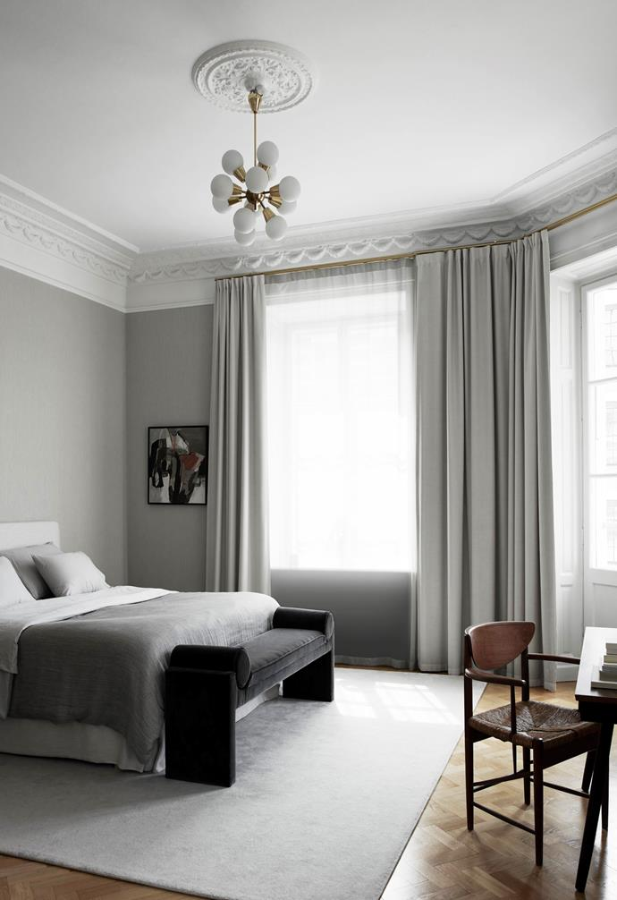A Sputnik pendant with gold detailing hangs from the ceiling in the master bedroom and ties neatly into the gold curtain rods. A vintage artwork Louise found at a French flea market serendipitously reflects its monochrome surrounds.