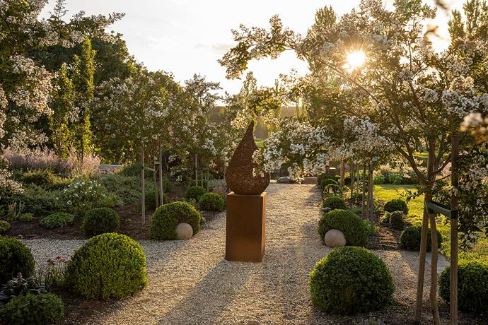 White flowering crepe myrtles, Lagerstroemia indica 'Natchez', line the main garden axis, which leads down to the billabong. A rusted-metal pear sculpture, from Wired For Living, Bendigo, creates a striking centrepiece and pausing point along the way.