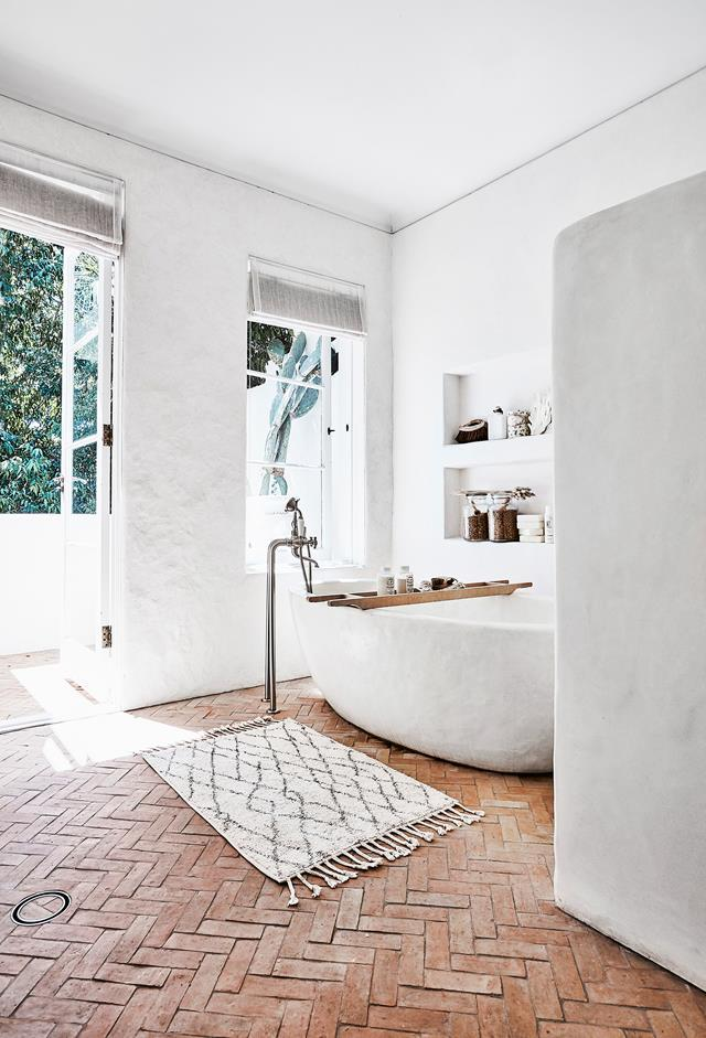 "The bathroom in stylist [Romi Weinberg's modern rustic home](https://www.homestolove.com.au/modern-rustic-interior-design-21024|target=""_blank"") features a Tadelakt plaster finish which pairs perfectly with the brick flooring covered by a small turkish rug. Photo: Maree Homer 