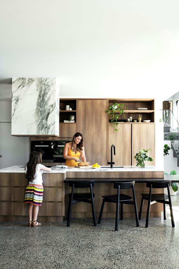 """Reminiscent of an edgy contemporary eatery, the kitchen, where Melanie enjoys arranging """"big, colourful platters"""", plays up the wood-and-stone combination to perfection, courtesy of Polytec cabinetry in Sepia Oak paired with Arabescato marble from WK Stone. """"I've always loved marble,"""" declares Melanie. The extractor is encased in the same stone that graces the benchtops, transforming a kitchen essential into a statement. """"It's like a piece of art for me,"""" says Melanie, who names it as one of her home's favourite features. """"I had friends that would say, 'Don't get marble because it marks and it's hard to keep in pristine condition,' but it was something that I've never, ever regretted."""" Pops of black (Reece's Sussex Scala mixer and Sketch Odd barstools from Globe West) add pizazz, while potted greenery creates a link to the verdant outdoors"""