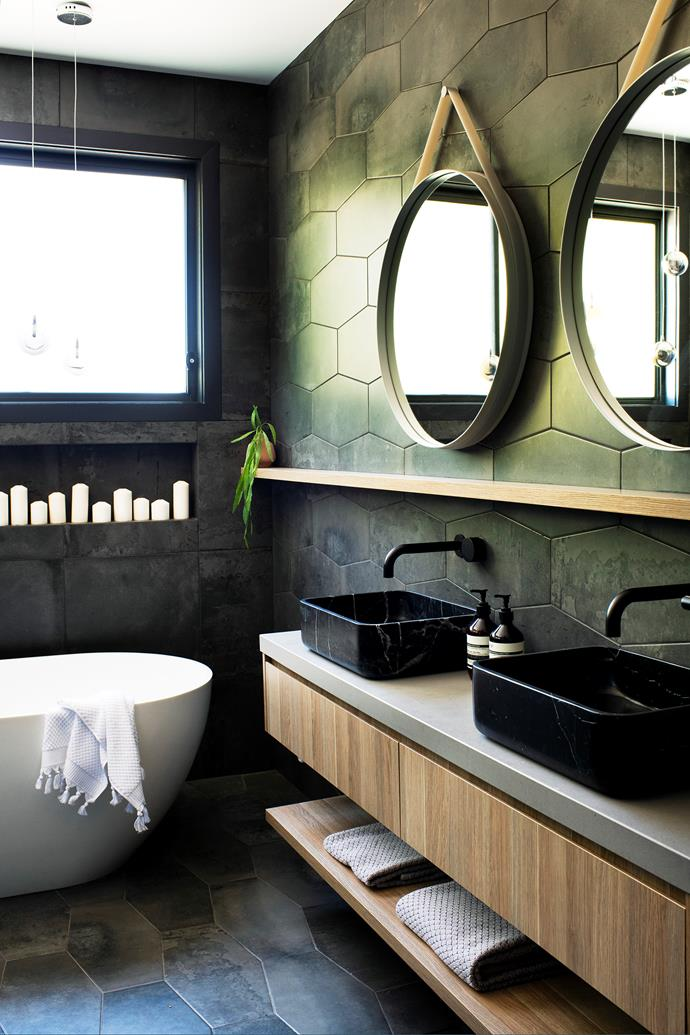 """""""The niche filled with candles lends itself to next-level sophistication,"""" says Sarah of the seductive ensuite, featuring a Clearwater Formoso freestanding bath and Factory Antracite Hexagonal tiles from Phillip's Tile Company in Port Kembla. A duo of black marble basins (seek similar at VidaXL), teamed with Reece's Milli Pure Progressive WBM tapware, ups the glam factor, as do the Cult Design mirrors. Melanie adds:""""I love the luxurious feel the dark tiles create."""""""