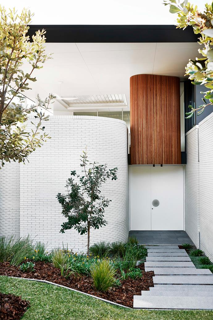 """A curvilinear facade created from white bricks creates a dramatic front entry for this [Palm Springs-inspired beach house](https://www.homestolove.com.au/palm-springs-style-beach-house-19258