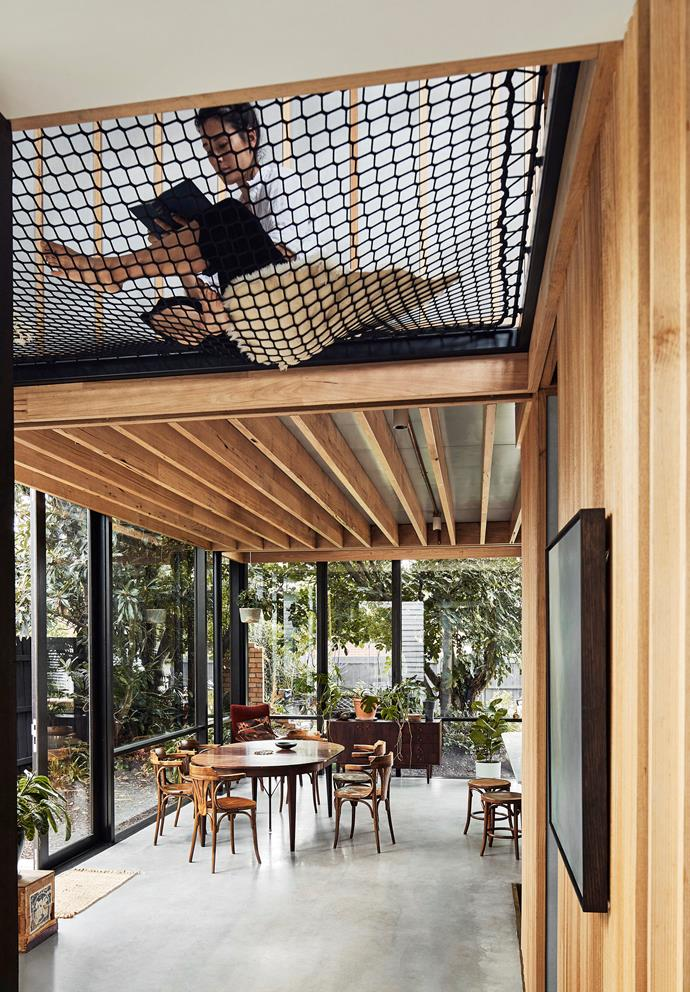 "Two double-storey voids are criss-crossed by nets, which delineate the upstairs reading and rumpus rooms. [Exposed beams](https://www.homestolove.com.au/exposed-timber-beams-20584|target=""_blank"") create extra height and guide the eye towards the garden."
