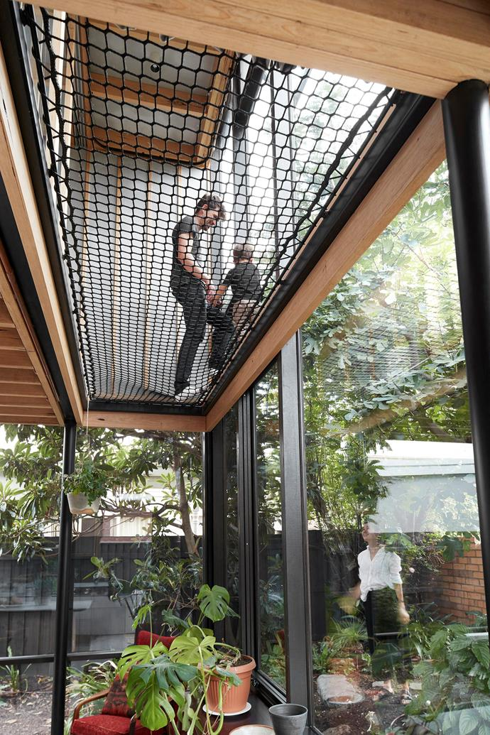 "With net floors beneath your feet and foliage within reach, the extension feels like a treehouse. ""We took the glass all the way to the ceiling so you can view the sky and not just the tree canopies, bringing light from the second level into the living space,"" Chris says."