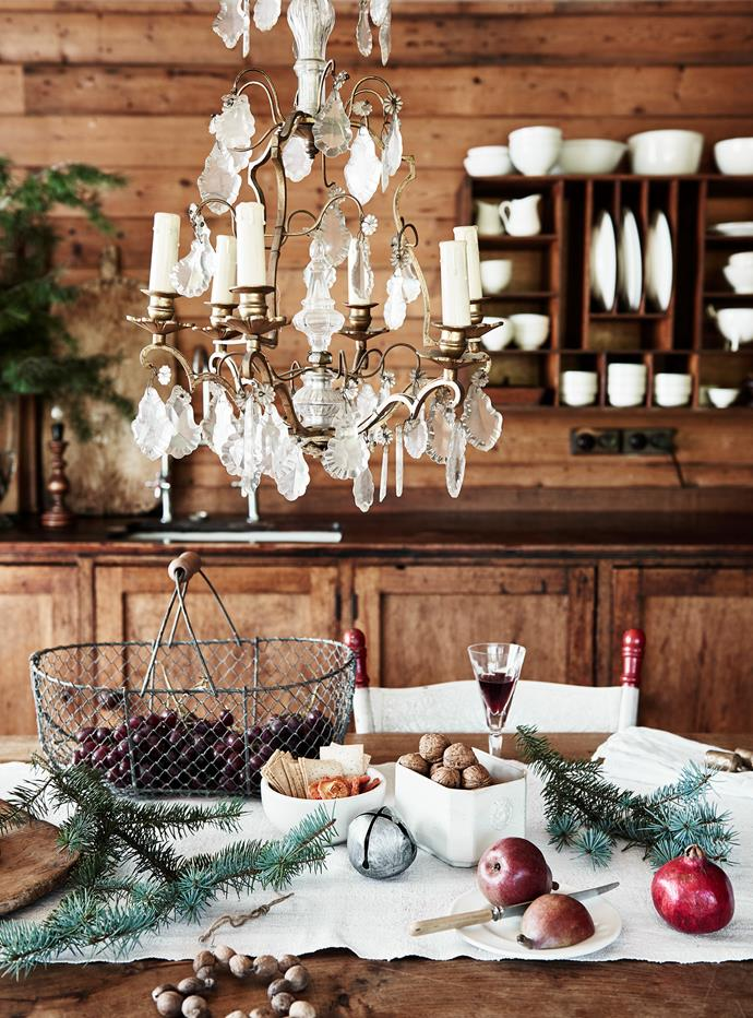 The antique French chandelier hangs low over the dining table, which is set for celebratory drinks. Helen stores her crockery in a repurposed cedar pigeonhole.