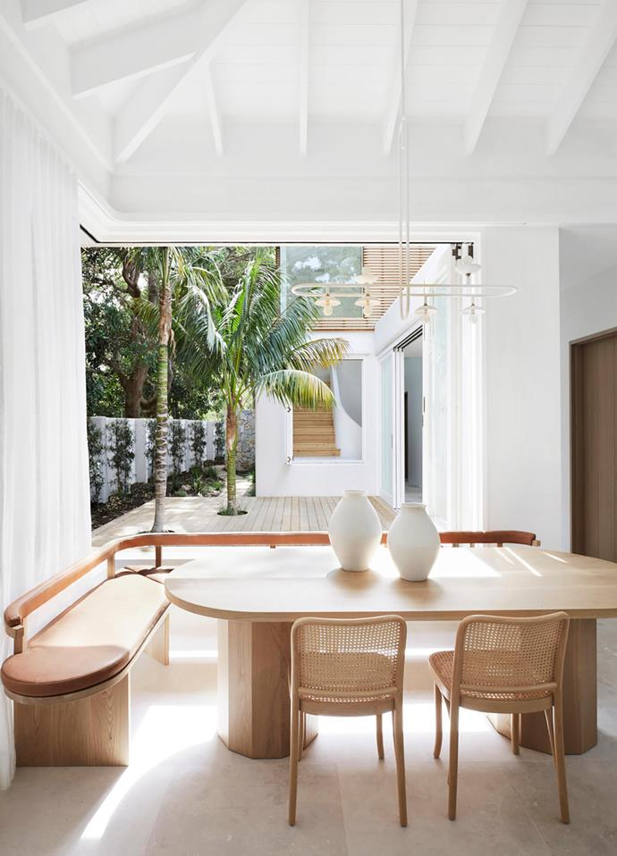 The airy dining area includes custom banquette seating and chairs from Thonet which surround a table from Mr and Mrs White. 'Paperclip' pendant light by Anna Charlesworth from Anchor Ceramics. Vases from Ondene and raw-sawn Aren Bianco limestone flooring from Onsite.