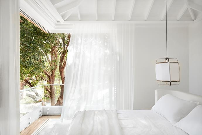 The master bedroom is a serene space where sheer white curtains frame the views and the bed is defined by a custom curved bedhead by CM Studio. Society Limonta throw from Ondene.