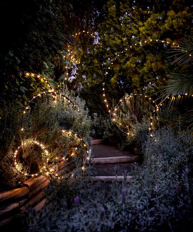 "Hang outdoor Christmas decorations in shrubs, trees and hedge, like this [magical garden filled with fairy lights](https://www.homestolove.com.au/using-fairy-lights-outside-5620|target=""_blank""). Story: Real Living"