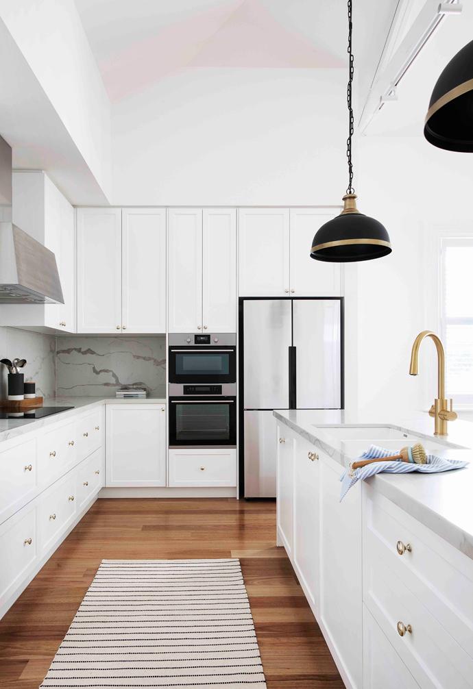 Brass accents warm up this neutral kitchen scheme. Photographer: Shania Shegedyn