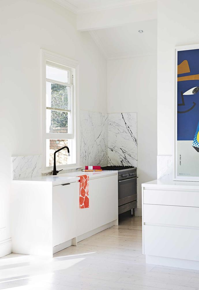 **Kitchen** The marble splashback provides a dramatic contrast to the stark-white palette of this compact kitchen space.