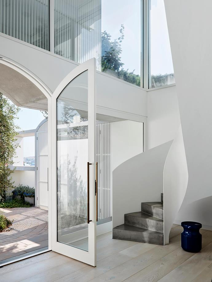 Accessed via a sunlit courtyard dappled with shade from a mature olive tree, the breezy, light-filled foyer creates a wonderful sense of arrival with its sweeping staircase gesturing visitors towards the upper floor.