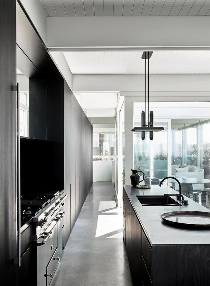 Dark timber joinery creates a stylish juxtaposition with the luminous white and grey surfaces deployed elsewhere. An Apparatus 'Circuit 4' pendant light from Criteria is suspended above the kitchen island.