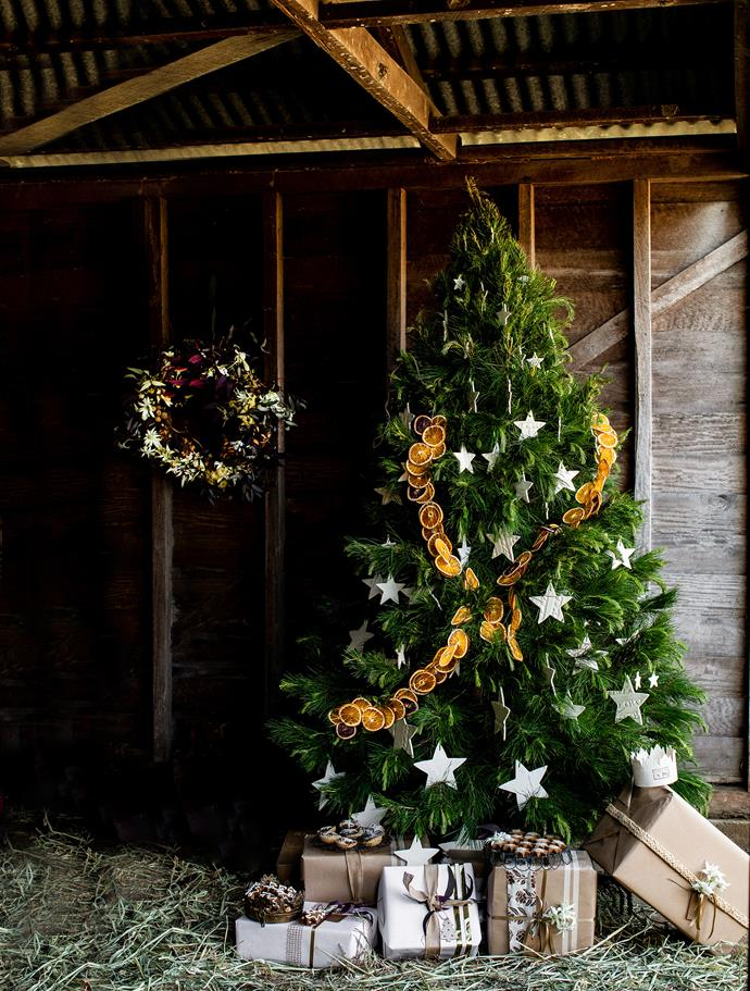 The real Christmas tree is decorated with an orange garland and ornaments from Paper Boat Press. The wreath is from Hacienda Flowers.