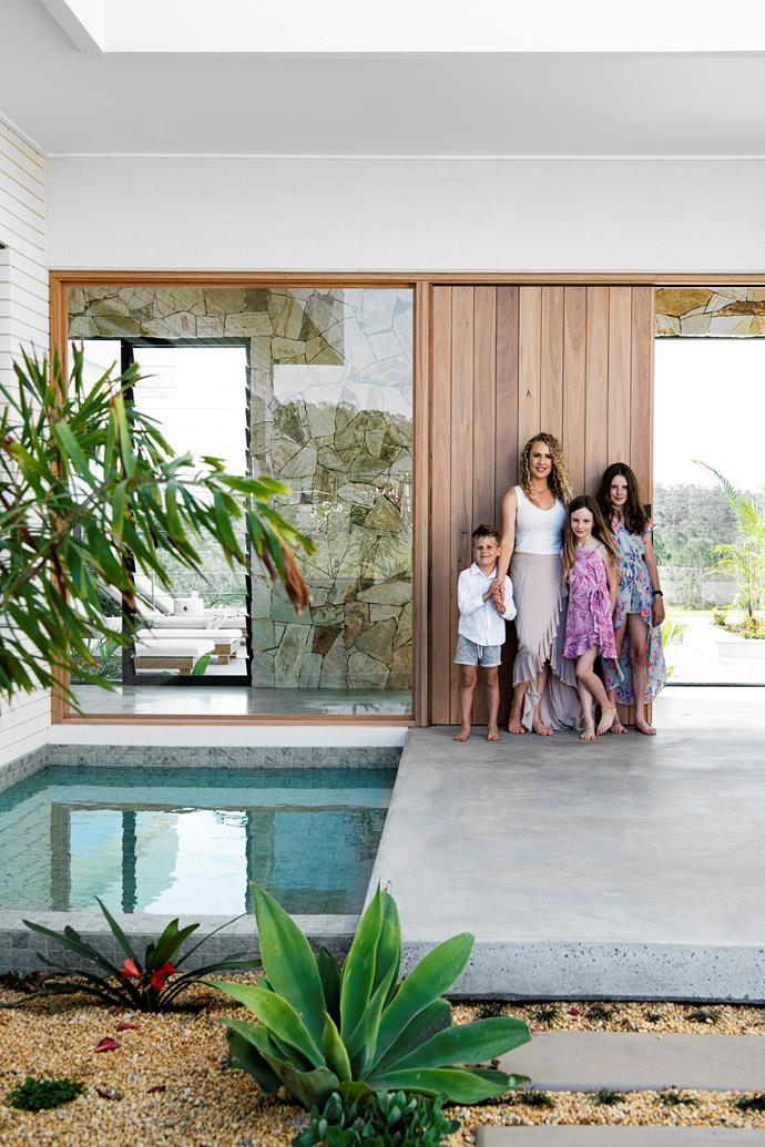 """We have lots of large windows,""says Sarah (pictured at her front door, complete with Balinese-style fish pond, with children, from left, Nate, Mylee and Chloe). ""Some are just fixed glass, and then we have louvred windows, because we really wanted to make the [home feel like a holiday](https://www.homestolove.com.au/holiday-at-home-ideas-2780