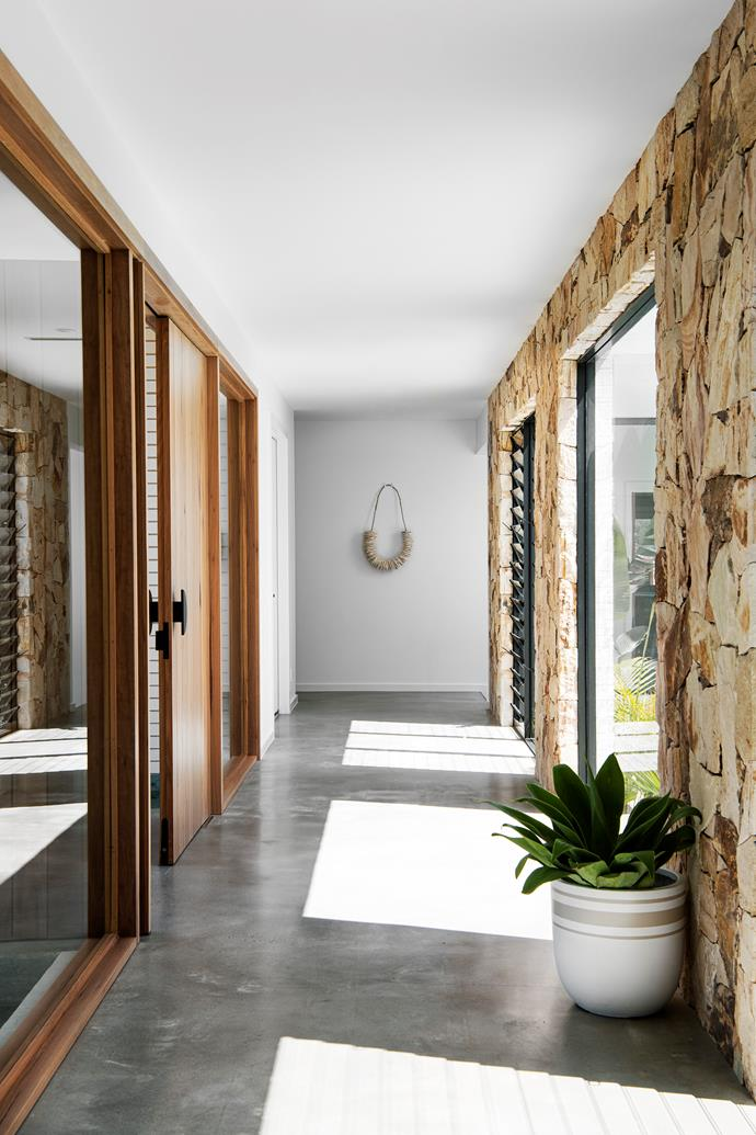 "In homage to the raw beauty of her home's setting, Sarah favoured natural materials, led by timber and stone. ""Natural stone runs through the whole length of the hallway,"" she notes, of the light-filled thoroughfare adorned simply by Mowgli Studio's 'Triple Stripe' pot and the 'Smiley' wall hanging from Let's Hang."