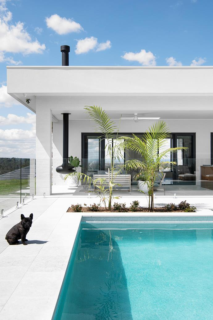 "Azure waters and an exterior painted in Taubmans Mt Everest echo the sky and clouds above, which is fitting, since Sarah and Jayden's home celebrates the great outdoors and epitomises [indoor-outdoor living](https://www.homestolove.com.au/12-indooroutdoor-ideas-for-a-stunning-entertaining-area-18680|target=""_blank""), with the pool (seen here with Leo striking a pose beside it) – which commands attention from every part of the house – unifying the two zones. ""The pool area flows seamlessly across the al fresco dining and lounge areas, then that is all connected to the kitchen, dining and living spaces,"" says Sarah. ""So, it's one big [outdoor area](https://www.homestolove.com.au/summer-outdoor-entertaining-ideas-18856