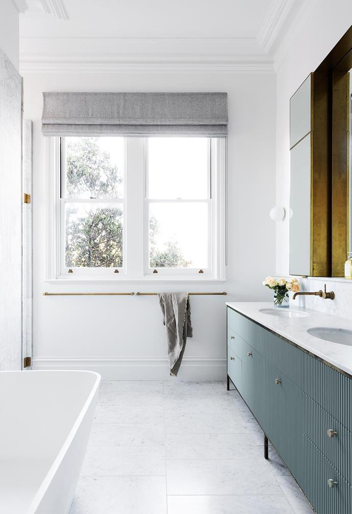 """The subtlety of the green ribbed panelling on the vanity works beautifully with the marble and brass in the bathroom of this [heritage Sydney abode](https://www.homestolove.com.au/heritage-family-home-sydney-21847