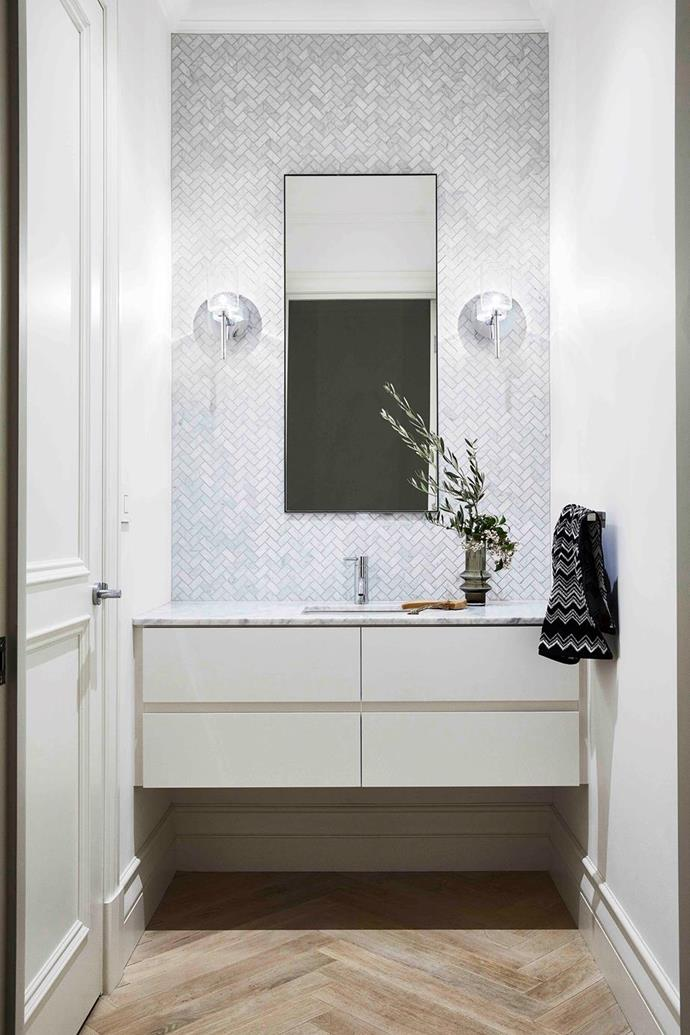 """Herringbone 'Bianco Carrara' marble mosaic tiles from Bespoke Tile & Stone by Earp Bros pack a tactile punch in the powder room of this [Spanish-style home in bayside Melbourne](https://www.homestolove.com.au/modern-spanish-style-home-melbourne-21563