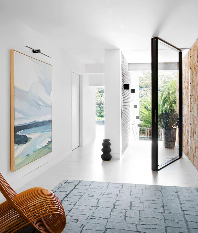 A large pivot door opens to the angled entry, which also functions as a gallery. Mexicana floor tiles, Bisanna Tiles. 'Going Up' rug, Robyn Cosgrove. Cappellini armchair, Cult. Marc wall lights, Urban Lighting. Artwork by Julian Meagher.
