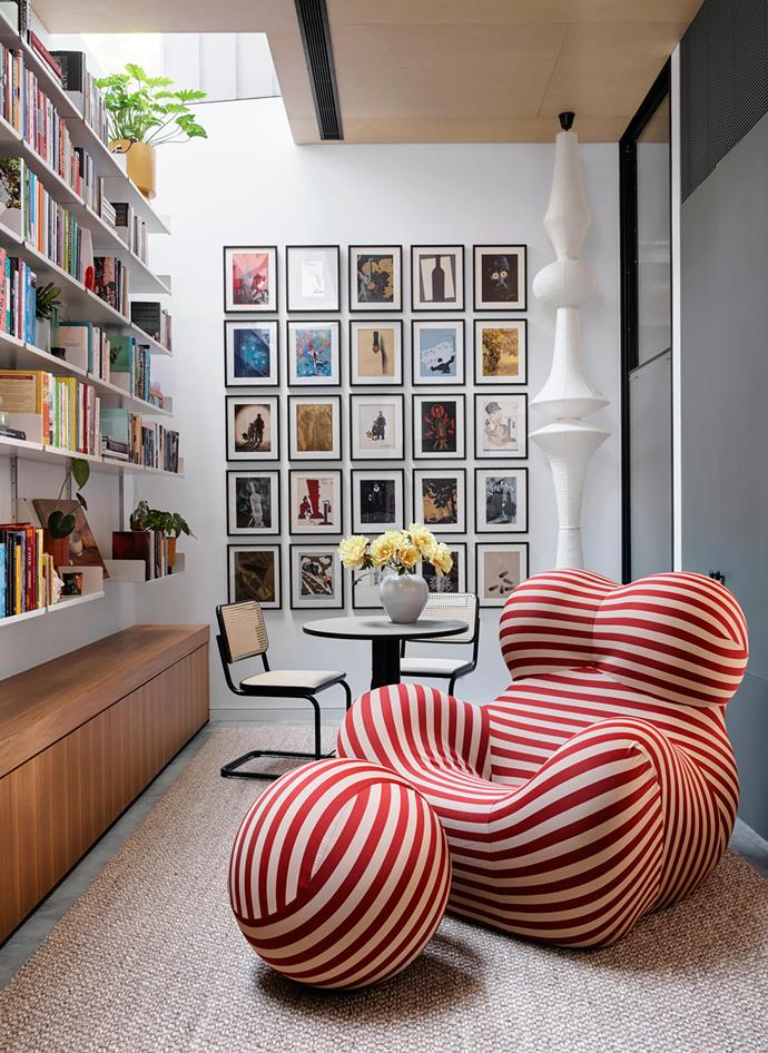 The library is lined with Vitsœ bookshelves by Dieter Rams and the client's collection of framed 1930s French wine posters. Vitra 'Akari E' pendant light by Isamu Noguchi from Living Edge, Thonet 'S 32' chairs from Anibou and B&B Italia 'Up Series 2000' armchair and ottoman from Space.