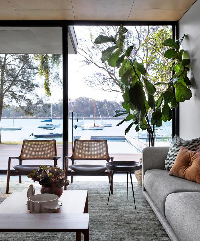 Floor-to-ceiling windows look out to the pool and harbour beyond, providing a beautiful backdrop to the living spaces. 'Mad' chairs in solid timber and woven rattan from Sollos Brazil with a Nau 'Molloy' timber coffee table stained in two tones and Mater 'Bowl' mango wood side table, both from Cult.