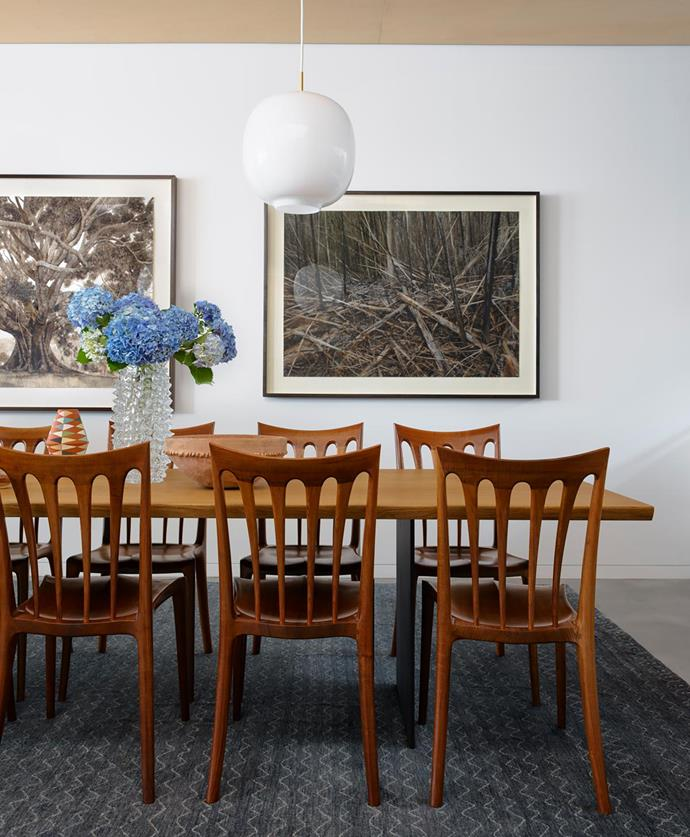 The client's vintage dining chairs surround a 'Tree' table from Great Dane on a 'Morocco 3' rug from Robyn Cosgrove. Artworks, Forest Collapse and Small Leaf Fig, by Nicholas Blowers.
