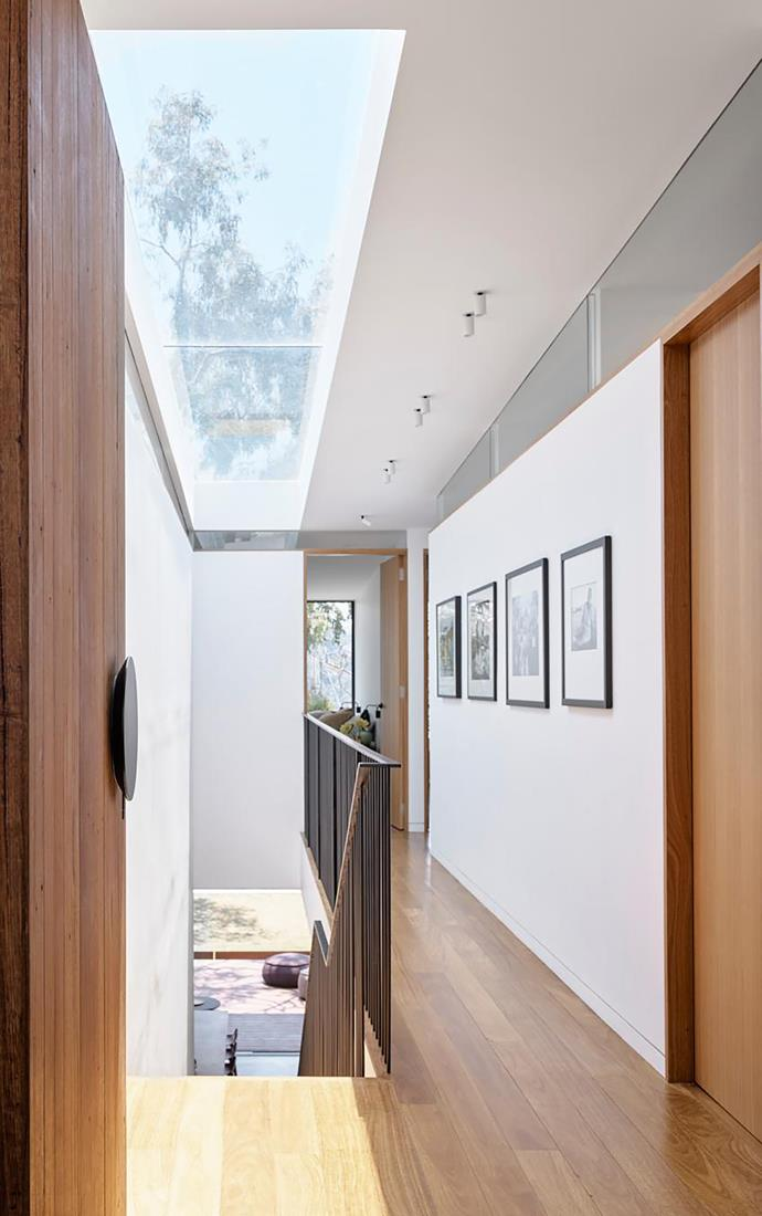 Looking from the entrance, photographic artworks depicting archetypal scenes of coastal Australia line the corridor over the stairwell, including Locals at Angourie Beach and Fresh Mullet, both by John Witzig, and Bondi Beach by Marco Bok.