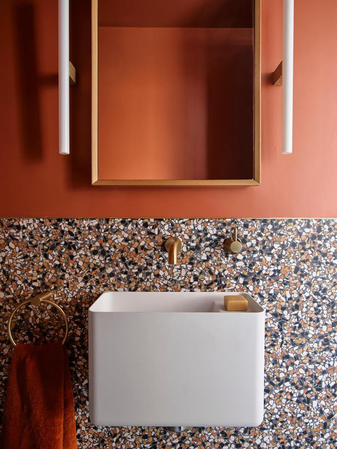 A shade of tomato tinged with nostalgia features in the powder room, where Nea 'Line of Light' wall lights from Kaia are positioned on either side of the vanity.