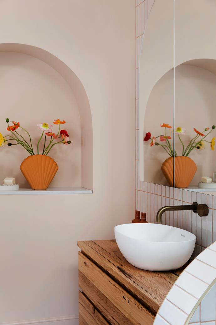 An arched mirror reflects the stunning recessed shelf.
