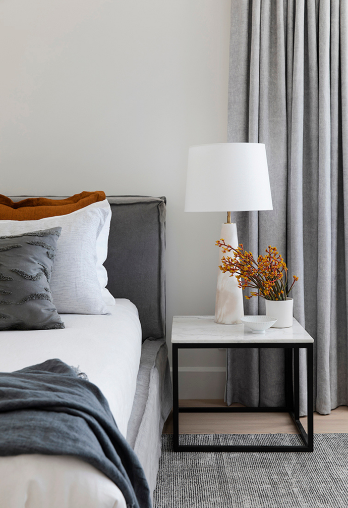 A sophisticated marble bedside table is paired with a marble lamp next to the bed.