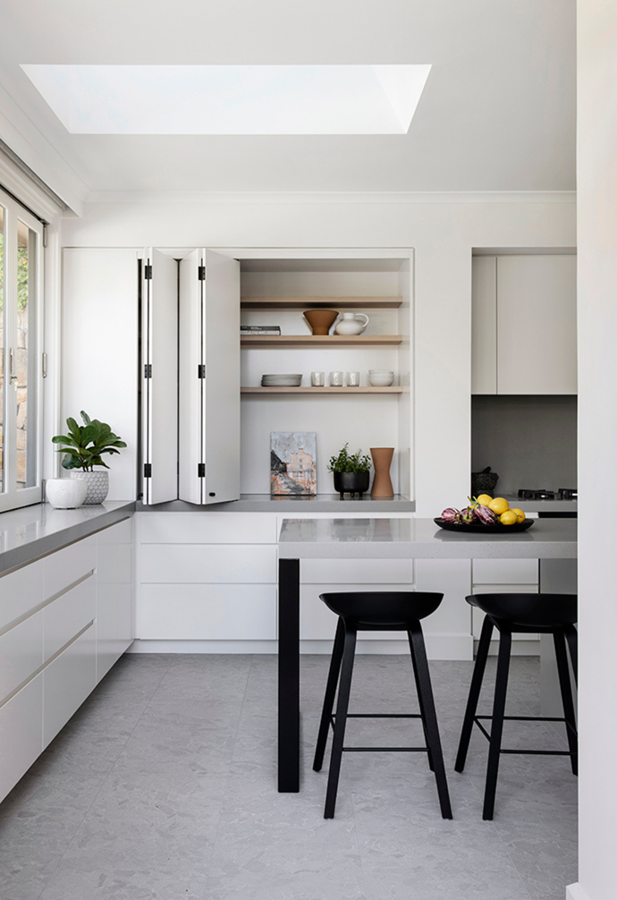 "Folding doors conceal an abundance of storage while a simple table island allows for flexible space in the kitchen. A [servery window](https://www.homestolove.com.au/kitchen-servery-windows-21477|target=""_blank"") makes it perfect for [outdoor entertaining](https://www.homestolove.com.au/how-to-create-an-outdoor-entertaining-area-18992