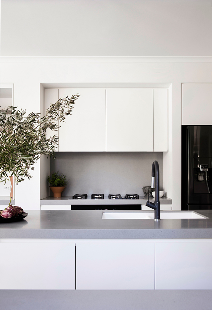 "In the [contemporary white kitchen](https://www.homestolove.com.au/all-white-sophisticated-kitchens-and-bathrooms-3019|target=""_blank""), black tap-ware and appliances stand out against the streamlined [cabinet doors](https://www.homestolove.com.au/kitchen-cabinet-door-styles-7021