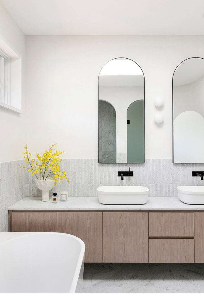 Curved mirrors and black tapware are elegant additions to the double vanity in the bathroom. Carrara marble floor tiles, marble finger tiles and an organic lime render plaster finish called Marrakesh was used in the bathrooms to complete the contemporary look.