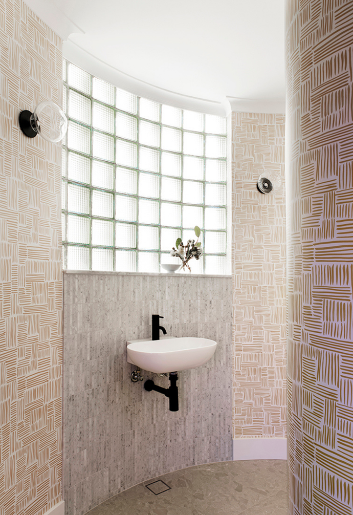 Carrara marble finger mosaic tiles are a striking feature in the pink-hued bathroom.