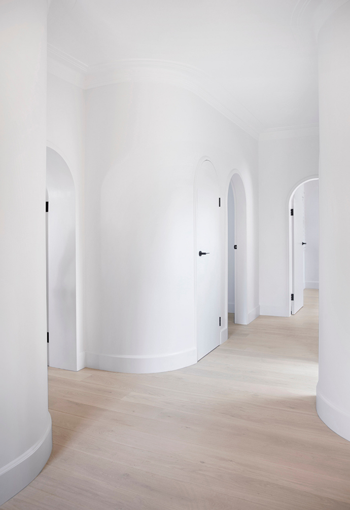 Custom matched cornice detail bring heritage character to the hallway of curves, with natural white walls throughout and white wash wide board oak engineered timber flooring.