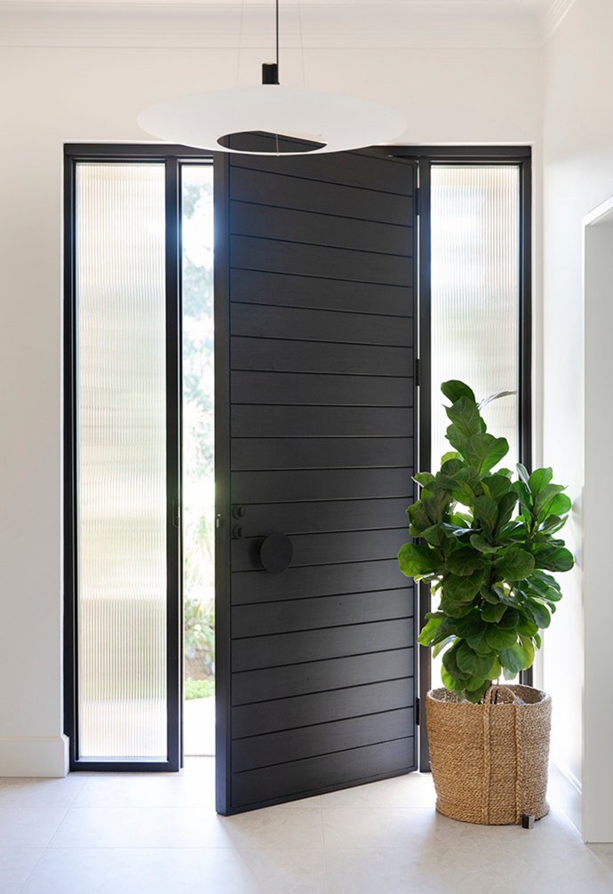 A matt black front door with fluted glass gives a modern welcome to the Art Deco home.