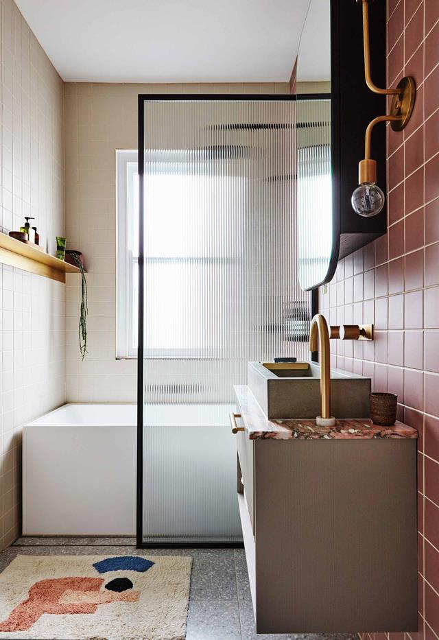 "The compact, considered [home of interior architect Sophie Bowers](https://www.homestolove.com.au/small-apartment-design-ideas-20593|target=""_blank"") is an absolute treat. The fluted-glass shower screen across the bath, Norwegian Rose marble vanity top and custom brass shelf add just the right amount of glamour while the Cold Picnic mat delivers a fun vibe."