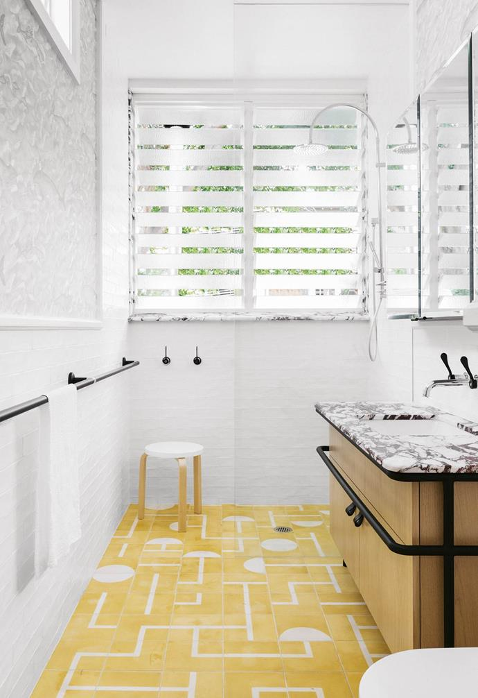 "The bright yellow tone and quirky patterned tiles make the flooring the star of this mostly white bathroom [designed by Arent&Pyke](https://www.homestolove.com.au/patterned-tiles-bathroom-20384|target=""_blank""). The irregular pattern creates a focal point that demands attention."